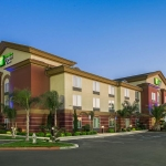 Holiday Inn Express & Suites Yosemite Pk Chowchilla building exterior in the early evening