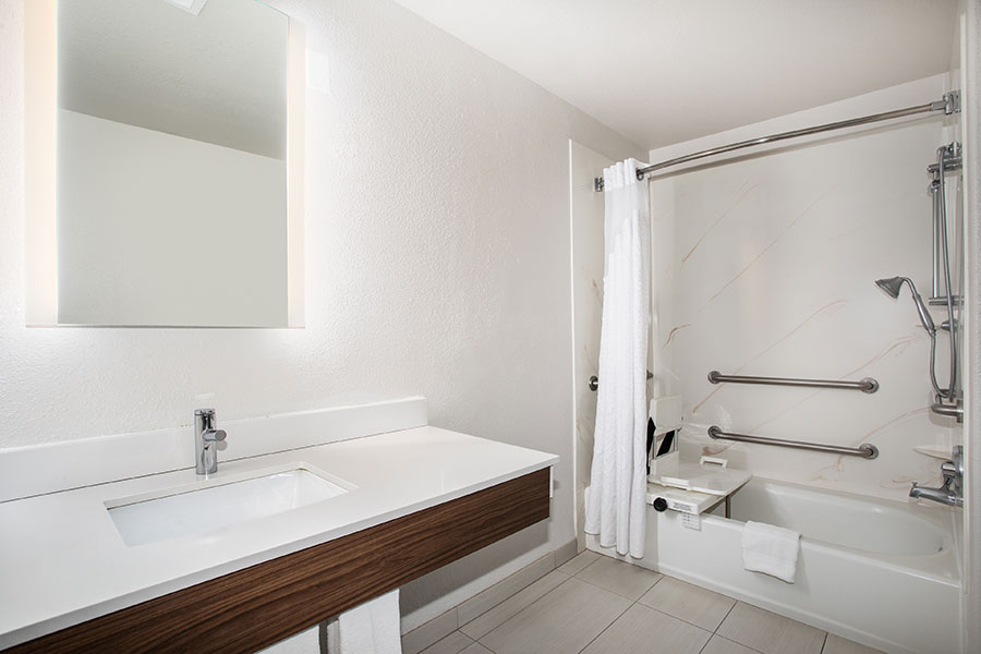 ADA accessible bathroom with accessible tub, grab bars, and shower seat